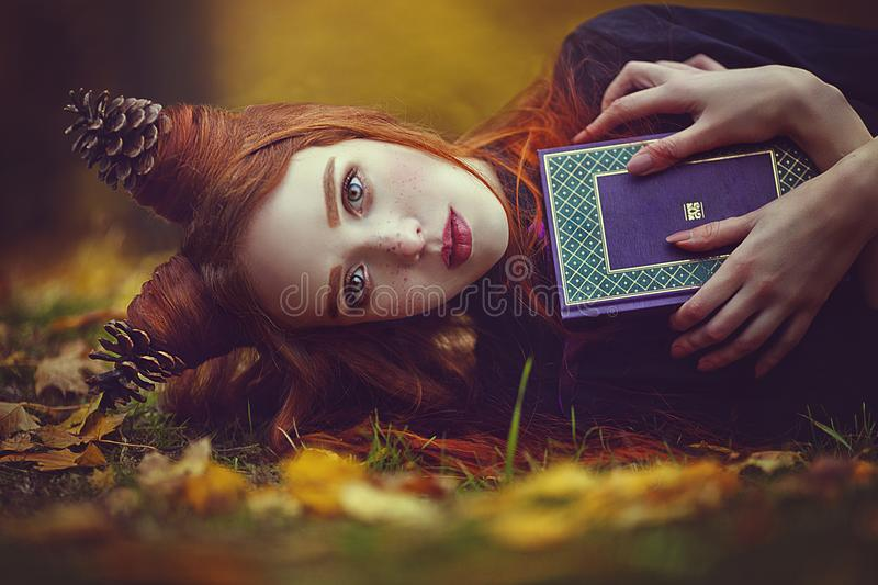 Portrait of a beautiful red-haired girl with an unusual hairdo with a book in the autumn fairy forest. A fabulous autumn. Photo shoot. Autumn season. Comfort royalty free stock photography