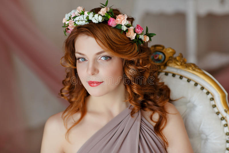 Portrait of a beautiful red-haired girl with a wreath of flowers stock images