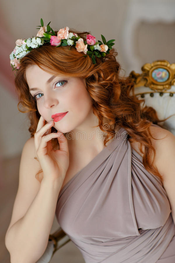 Portrait of a beautiful red-haired girl with a wreath of flowers royalty free stock images