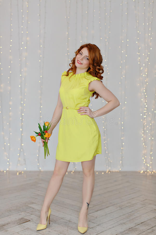 Portrait of a beautiful red-haired girl in a yellow dress holding a tulip on the background of lights, full height stock image