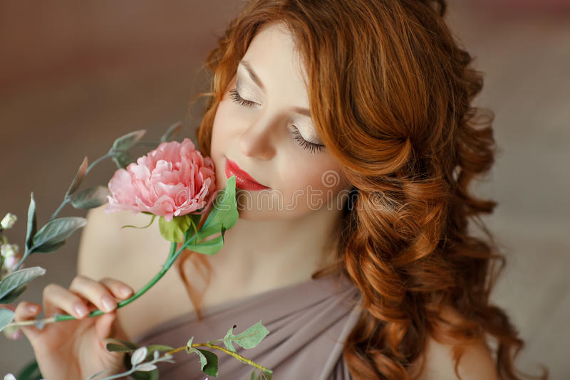 Portrait of a beautiful red-haired laughing girl with blue eyes, smelling a flower, in the spring interiors royalty free stock photography