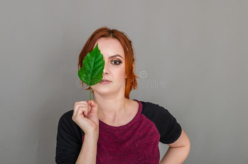 Portrait of a beautiful red-haired woman, half of her face closed by a large green leaf of a Chinese rose. Women`s health, natura stock photo
