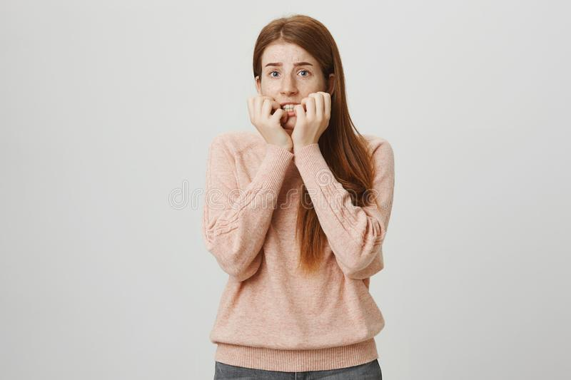 Portrait of beautiful redhead european woman expressing fright, being scared and holding hands near mouth, staring aside stock photography