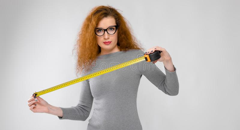 Portrait of beautiful redhead happy smiling young woman in gray clothes in glasses holding tape measure on gray stock images