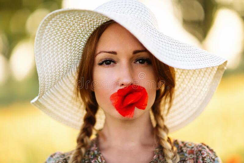 Portrait of beautiful redhead woman in white hat on green field with poppy flower in her mouth stock images