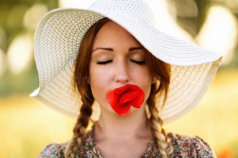 Portrait of beautiful redhead woman in white hat on green field with poppy flower in her mouth royalty free stock photo