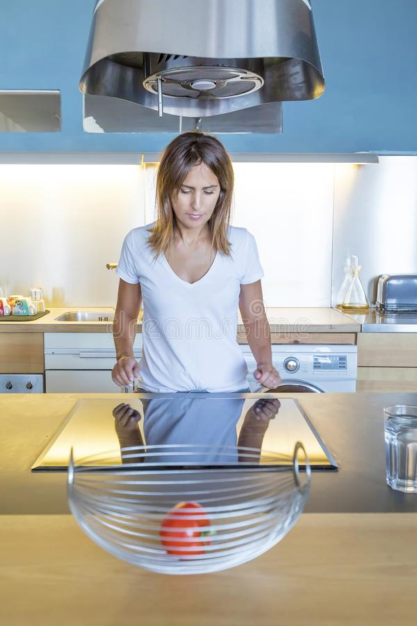Portrait of beautiful relaxed young woman in the her kitchen stock photography