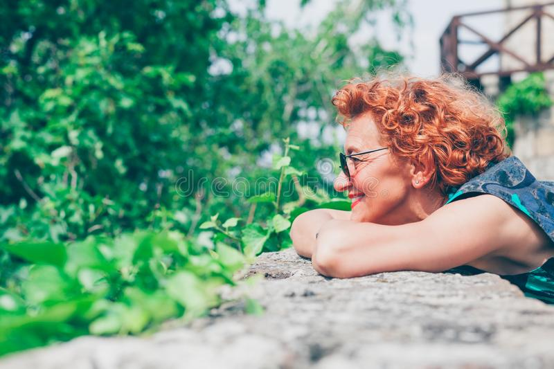 Beautiful retro older woman in front of the brick wall royalty free stock photography