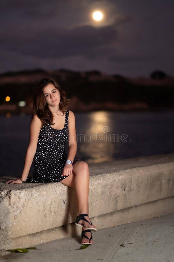 Beautiful romantic girl with the moon shining on the ocean royalty free stock image