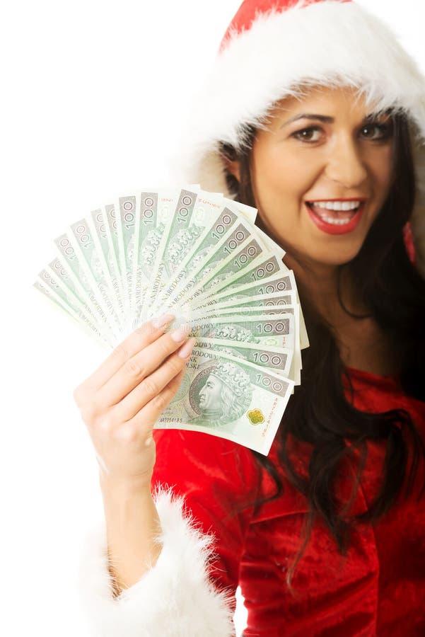 Portrait beautiful santa woman holding a clip of polish money stock photo