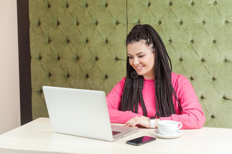 Portrait of beautiful satisfied young woman freelancer with black dreadlocks hairstyle in pink blouse are sitting in cafe and stock photo