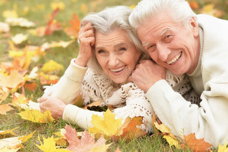 Portrait of beautiful senior couple lying on grass stock images
