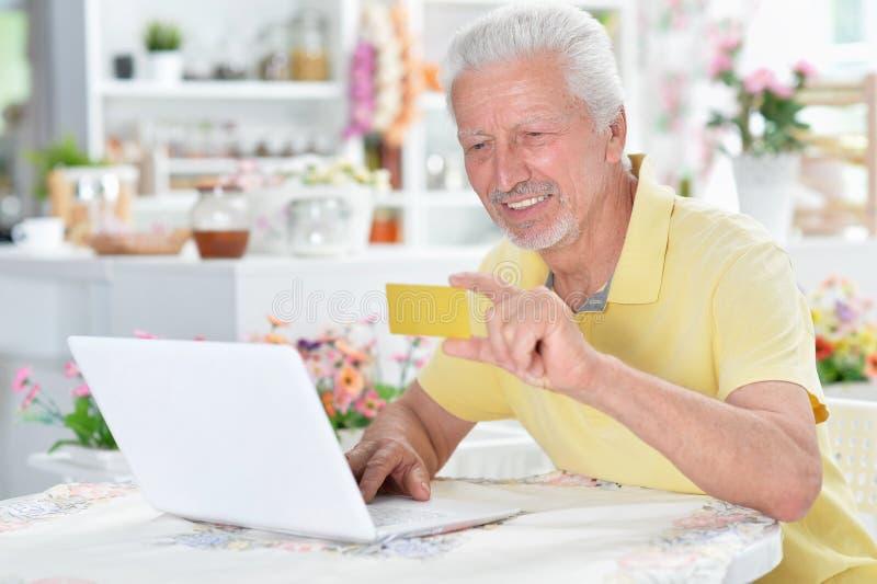 Portrait of beautiful senior man using laptop at home royalty free stock image