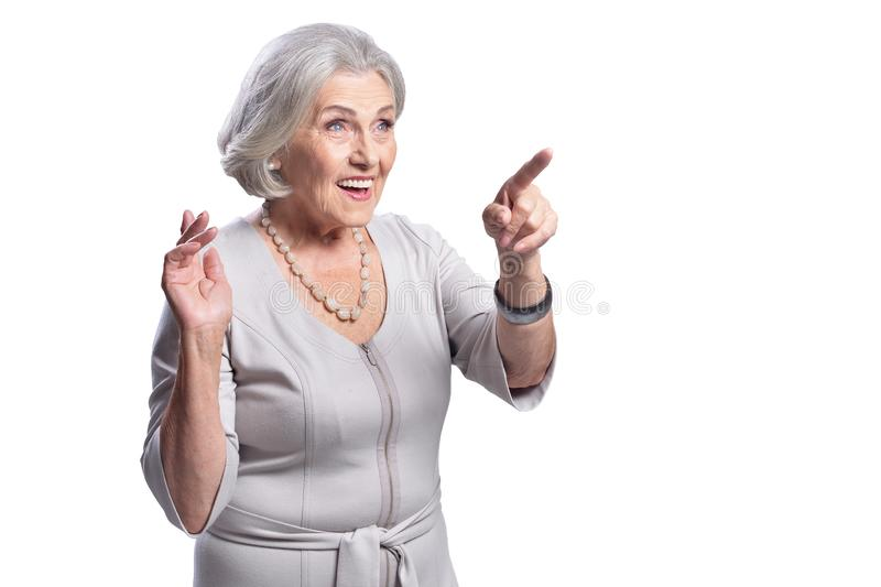 Portrait of beautiful senior woman pointing to the right stock photography