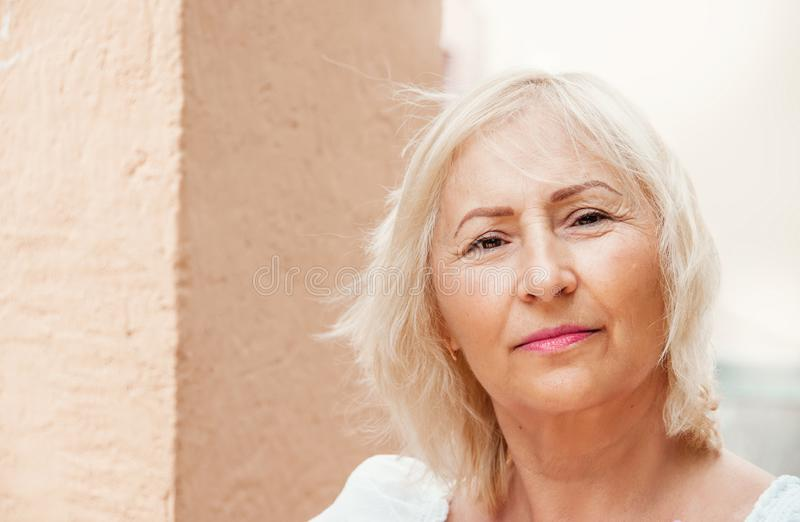 Portrait of beautiful senior woman with white hair standing by w stock photos