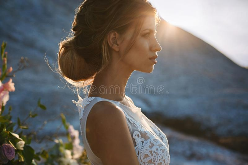 Portrait of beautiful and sensual blonde model girl with modeling stylish hairstyle in fashionable white lace dress posing at the royalty free stock photo