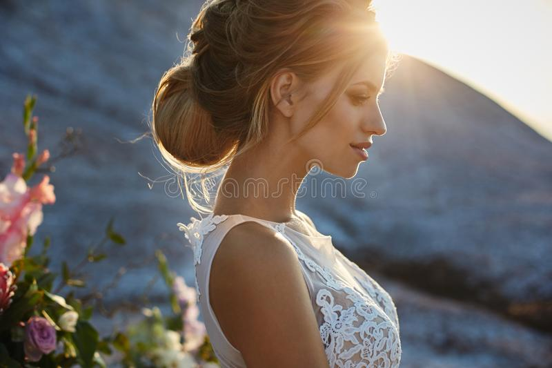 Portrait of beautiful and sensual blonde model girl with modeling stylish hairstyle in fashionable white lace dress posing at the royalty free stock images