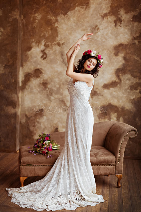 Portrait of beautiful sensual brunette girl in a white lace dress, with a wreath of flowers on her head, in full growth on a brow stock image