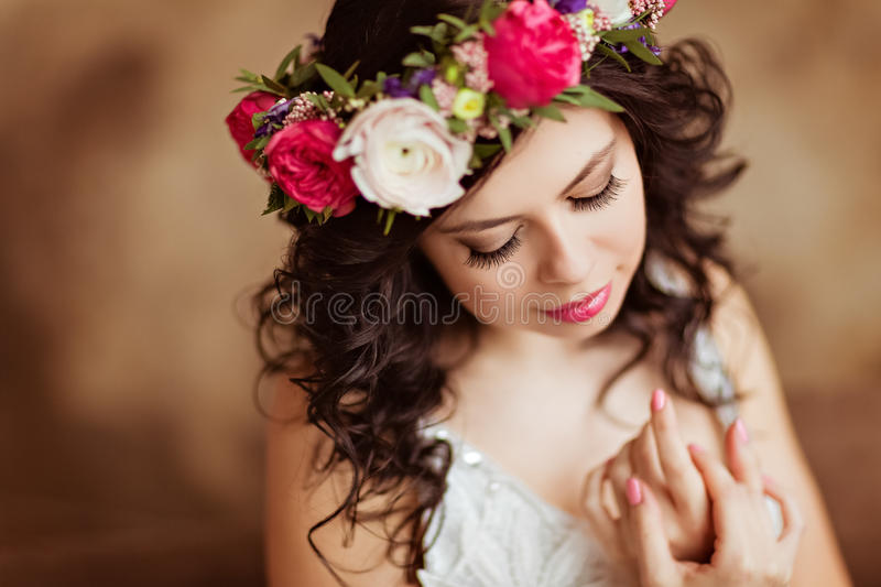 Portrait of beautiful sensual brunette girl in a white lace dress, with a wreath of flowers on his head, on a brown background in royalty free stock photos