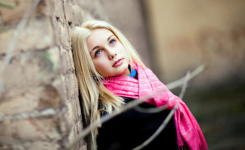 Portrait of beautiful sensual girl with thick blond hair, looking up, in a black coat and a pink scarf in the fall royalty free stock photos