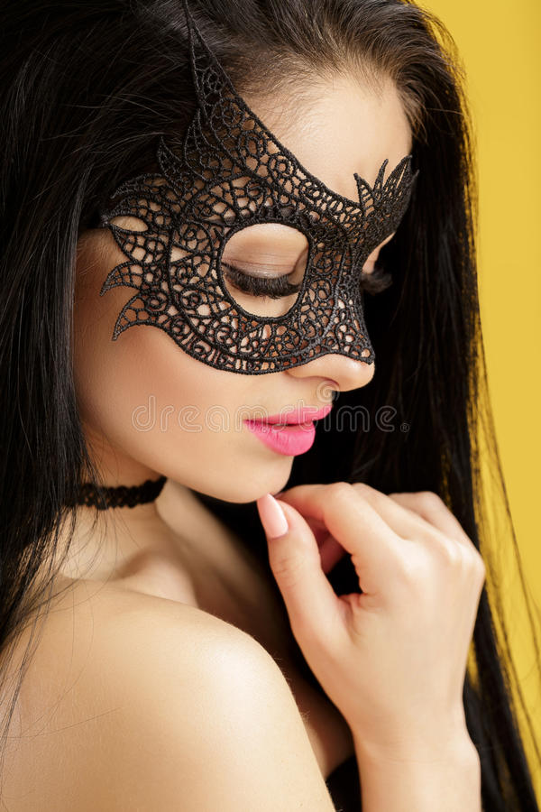 Portrait of beautiful sensual woman in black lace mask on yellow background. girl in venetian mask. Portrait of beautiful sensual woman in black lace mask on the stock images