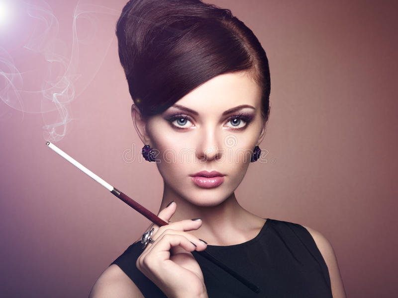 Portrait of beautiful sensual woman with elegant hairstyle. Woman with cigarette Perfect makeup. Fashion photo stock image