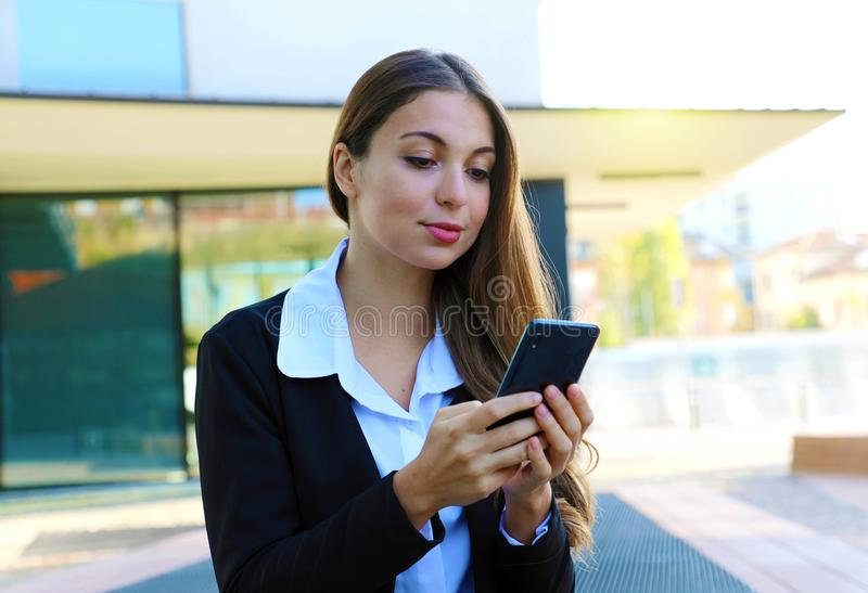 Portrait of beautiful serious business woman typing with smart phone outdoors royalty free stock photo