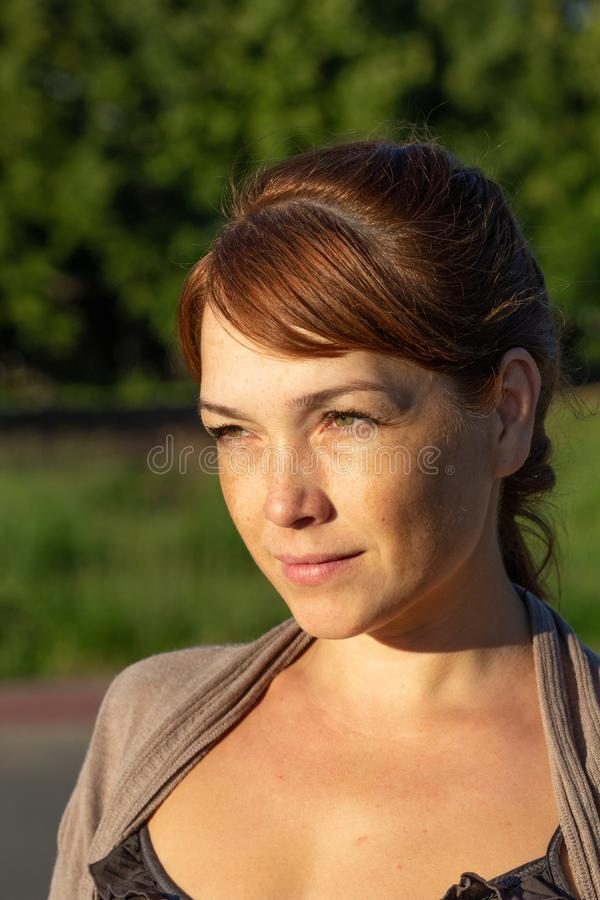 Portrait of beautiful serious middle-aged woman with calm face looking aside in summer green park stock photography