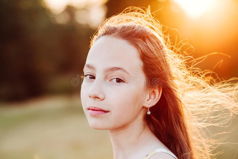 Portrait of Beautiful serious Teen Girl is enjoying nature in the park at Summer sunset royalty free stock image