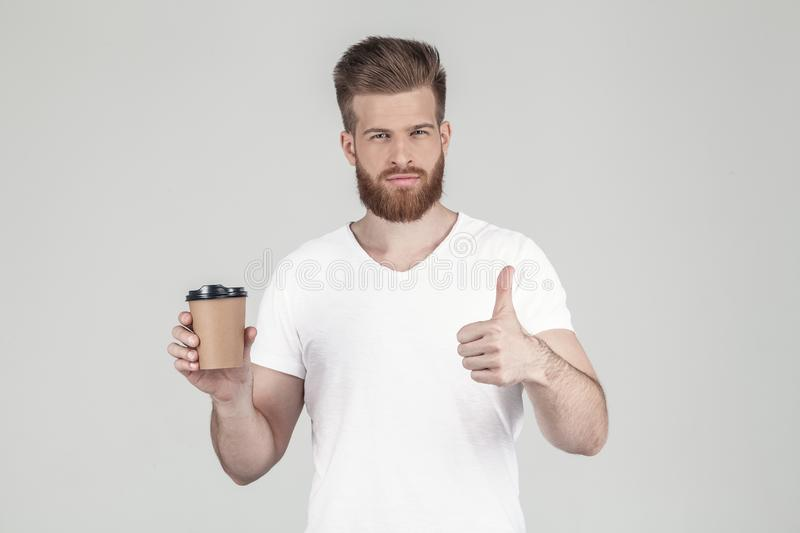 A portrait of a beautiful sex hipster dressed in a white T-shirt holds a cup of coffee in one hand and the other shows stock photo