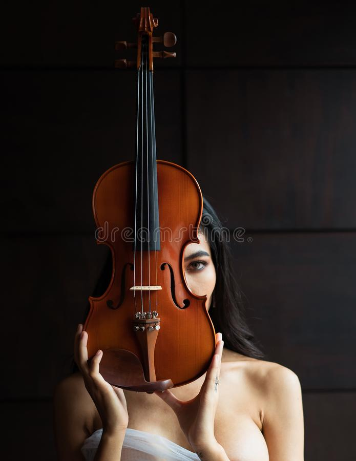 Portrait of beautiful sexy Asian woman with violin posing with it in front and middle of her face looking at camera royalty free stock photo
