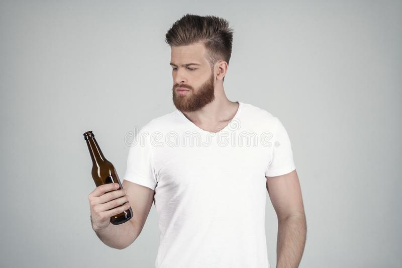 Portrait of a beautiful sexy bearded man dressed in a white T-shirt holds a bottle of beer in his hand. he stands in stock photography