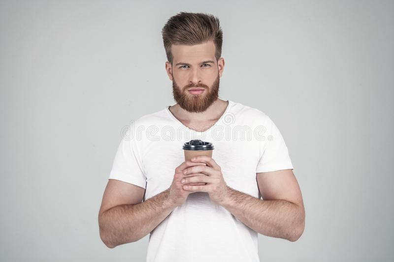 Portrait of a beautiful sexy bearded man dressed in a white T-shirt holds the coffee with two hands and looks at the royalty free stock photo