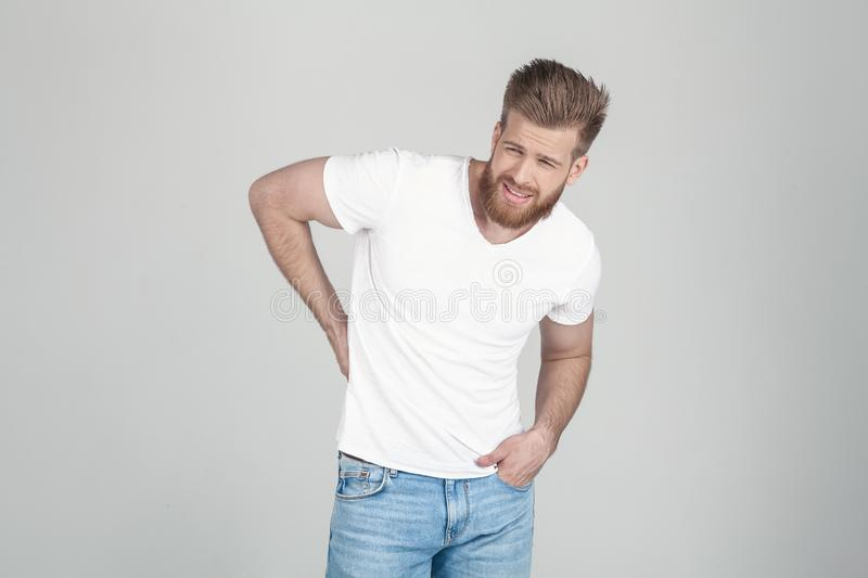 Portrait of beautiful sexy bearded man. Holds behind his back. he has a back pain he stands in front of a white background stock photography