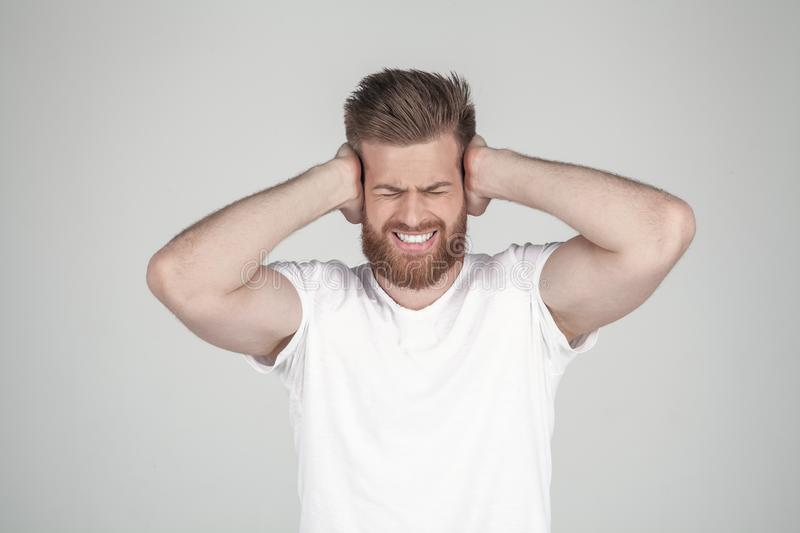 Portrait of beautiful sexy bearded man. holds his arms behind his head and shouts. he has a headache, he stands in front of the royalty free stock photography