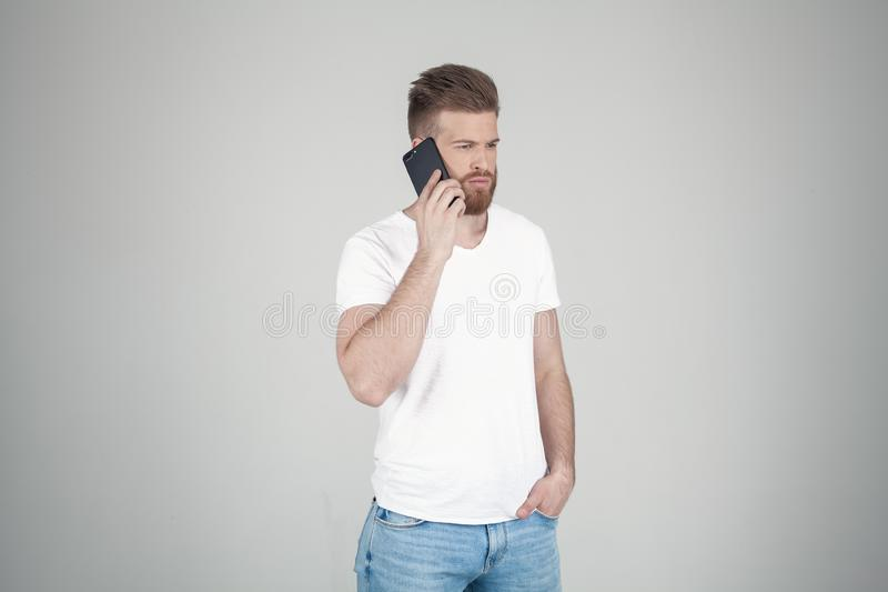 Portrait of beautiful sexy bearded man. he stands in the profile and talks over the phone. he stands in front of the white stock images
