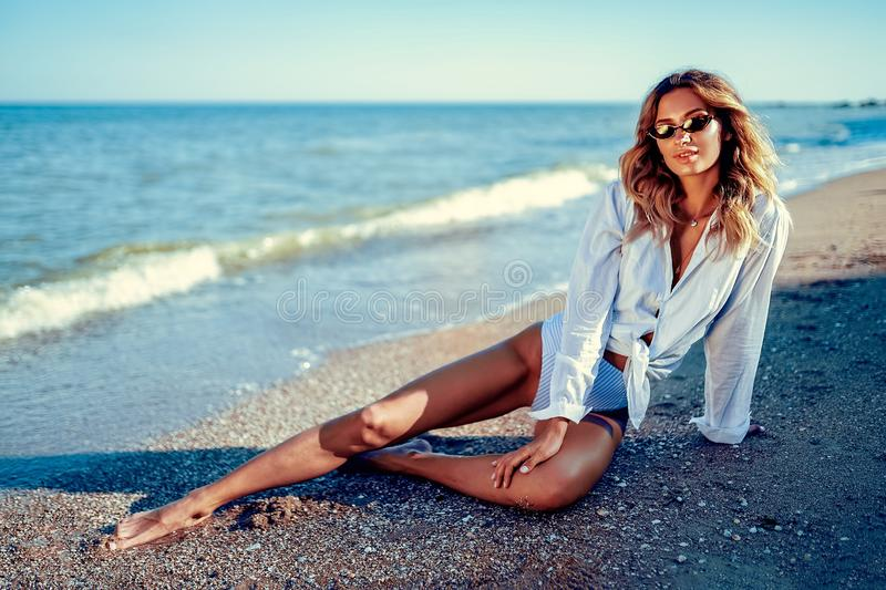 Portrait of beautiful sexy caucasian sunbathed woman in sunglasses with long hair in swimsuit lying on summer beach royalty free stock images