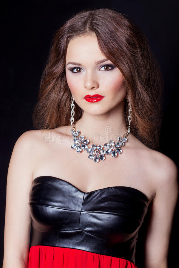 Portrait of a beautiful elegant girl in evening dress with a large necklace with a bright festive makeup Studio stock images