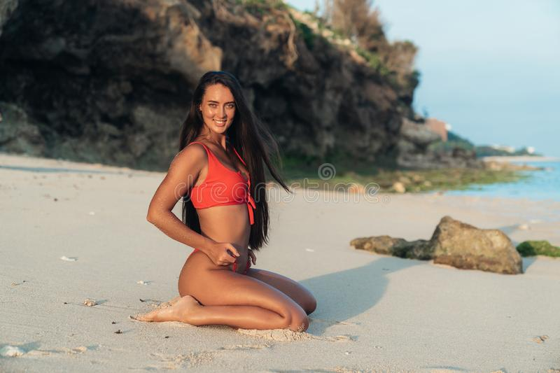 Portrait of beautiful sexy girl in red swimwear with long hair posing on beach with white sand. Brunette model enjoys relaxing near ocean. Concept travel stock photo