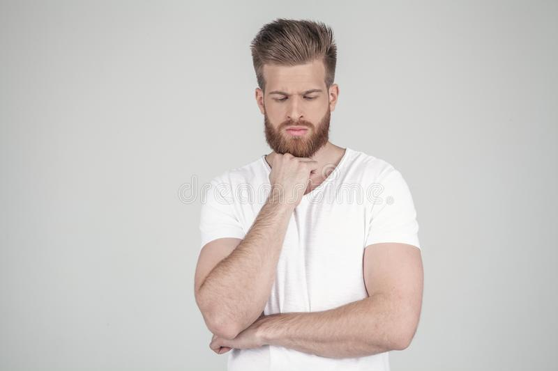 Portrait of a beautiful sexy hipster dressed in a white T-shirt. Conceived holds his hand at the chin. he stands in stock image