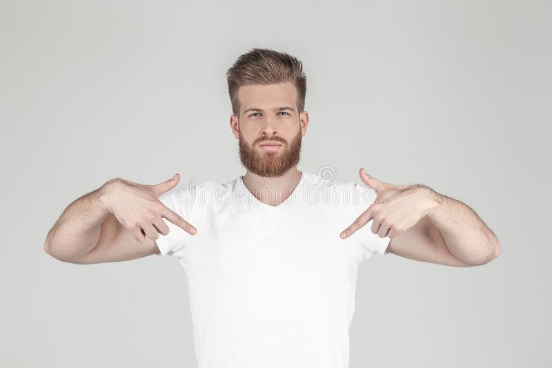 Portrait of a beautiful sexy hipster dressed in a white T-shirt. Shows hands on his T-shirt. place for your logo or stock images