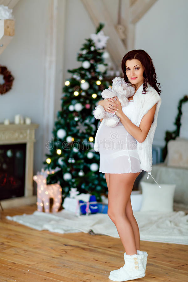 Portrait of beautiful pregnant brunette in white transparen. T peignoir, holding a stuffed toy bear , in the interior near the Christmas tree and fireplace stock image
