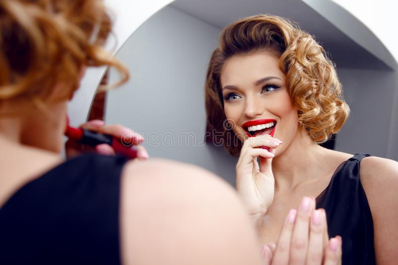 Beautiful sensual young woman applying red lipstick on lips looking at mirror. Beautiful woman makes evening makeup stock image