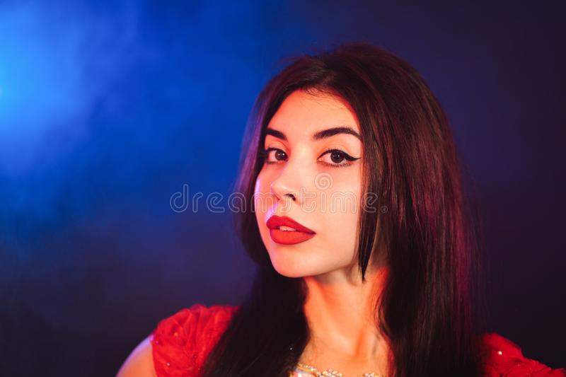 Portrait of beautiful traditional oriental belly dancer girl on blue neon smoky background. Woman in red exotic. Costume royalty free stock image