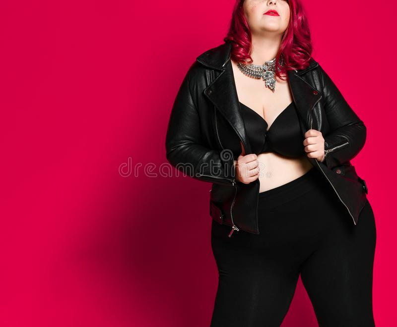 Portrait of a beautiful sexy woman in black leather jacket. Hot sexy chubby red-haired woman in a black leather jacket and black bra, tight-fitting pants and a stock images