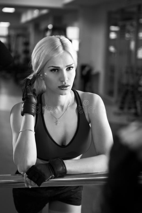 Portrait of a beautiful woman dressed in sports clothes in the gym stock image