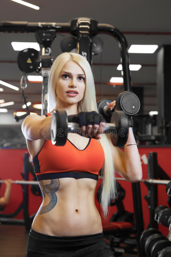 Portrait of a beautiful woman dressed in sports clothes in the gym royalty free stock images