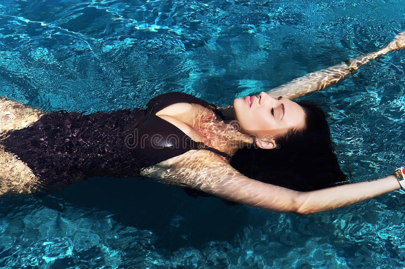 Portrait of a beautiful woman swimming in the pool stock photography