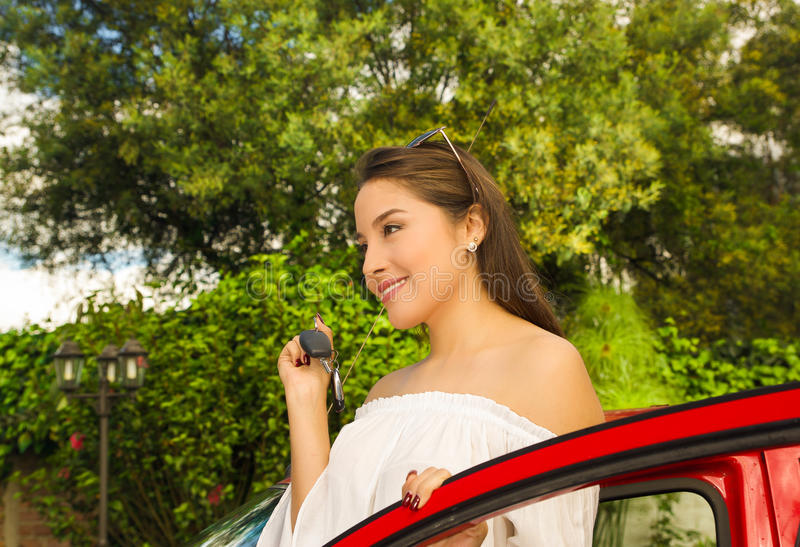 Portrait of a beautiful young woman in red car holding keys and smiling.  royalty free stock photos