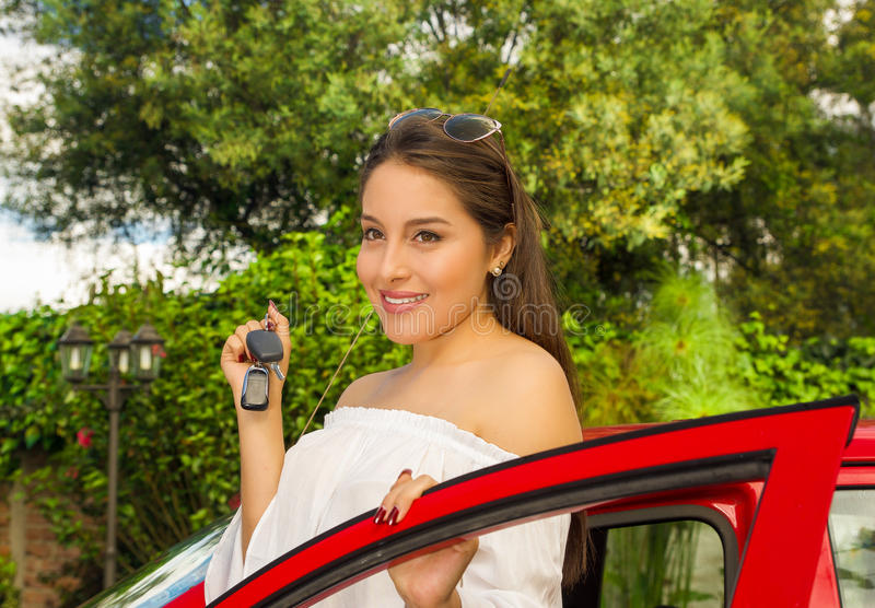 Portrait of a beautiful young woman in red car holding keys and smiling.  stock photos